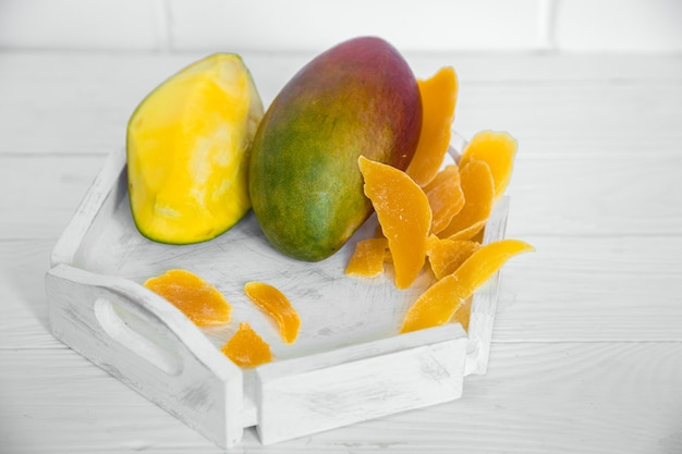ジュースと白い木製のトレイ、健康食品とエキゾチックなフルーツのコンセプトにドライマンゴーと白い木製の背景にマンゴー