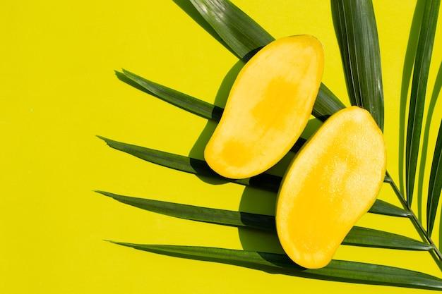 黄色の背景に緑の葉にマンゴー。