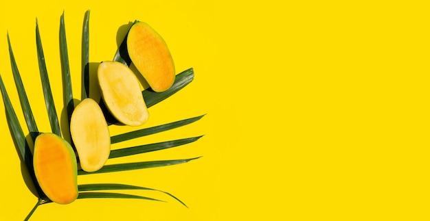 黄色い表面に熱帯のヤシの葉にマンゴー