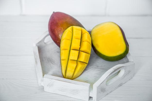 白い木製の背景にマンゴー