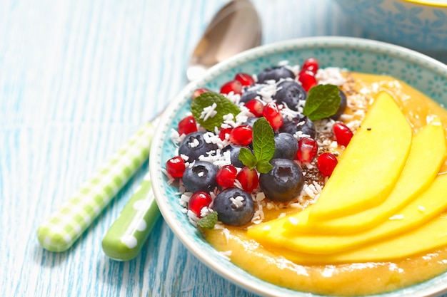 Mango orange banana smoothie with berries topping in a bowl
