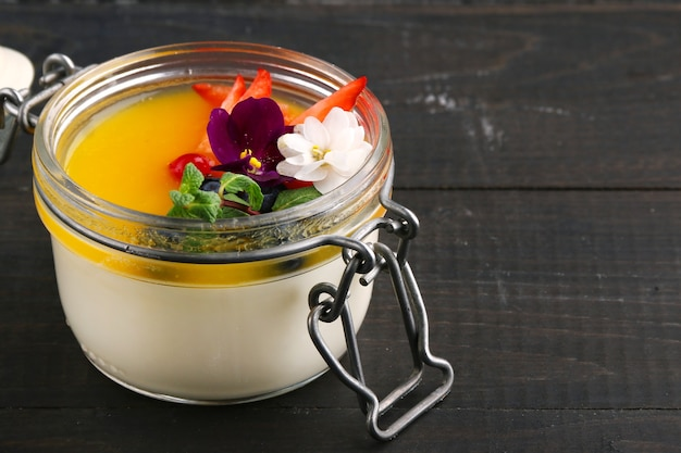 Mango panna cotta with flower and mint close up on wooden table.
