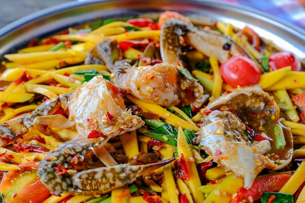 Mango papaya salad with blue crab placed in a beautifully placed tray on a thai style wooden table