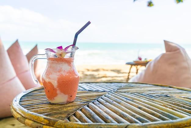 マンゴー、パイナップル、スイカ、ヨーグルトまたはヨーグルトのスムージージャーと海のビーチ