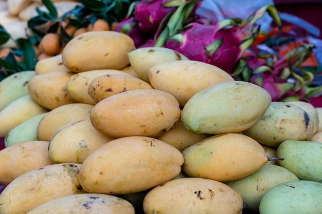 태국 현지 거리 시장에서 판매되는 망고, 피타하야, 마리안 자두. 열대 과일을 닫습니다.
