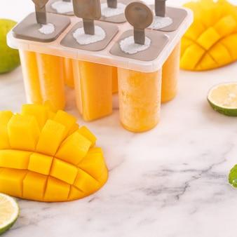 マンゴーアイスキャンディー、明るい大理石のテーブルのプラスチック成形ボックスのフルーツアイス。夏のリフレッシュメントコンセプト製品のデザイン要素、オブジェクト、クローズアップ。