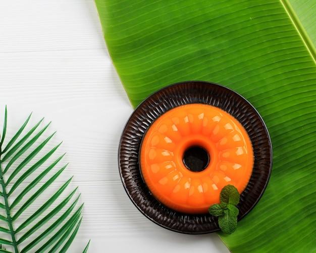 Пудинг из манго для свежего лета. подавать над банановым листом, черная тарелка
