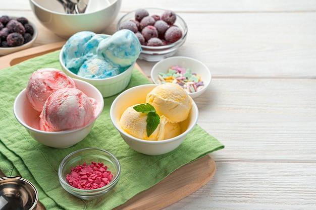 Мороженое из манго, малины и ежевики на светлой стене с пространством для копирования. вид сбоку, крупный план. летний десерт.