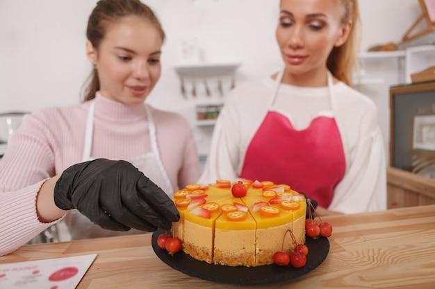 女性の菓子職人の手にマンゴー生ビーガンケーキ