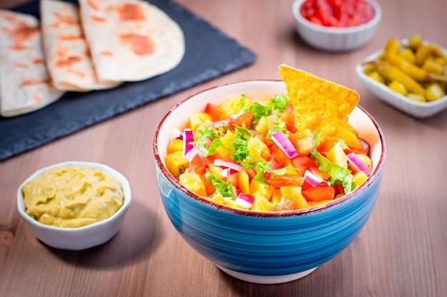 マンゴーサルサはハラペーニョペッパー、トルティーヤ、ライムでクローズアップします。シンコデマヨのお祝いパーティーの伝統的な料理と前菜。上面図