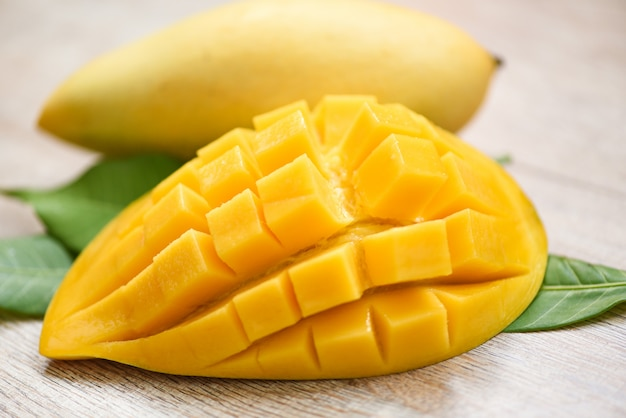 Mango slice and mango leaves from tree tropical summer fruit concept - sweet ripe mangos cut half