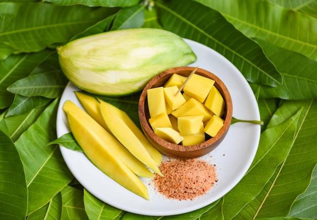 トロピカルサマーフルーツコンセプト-完熟マンゴーとスナックのグリーンマンゴーから白いプレートと緑の葉のマンゴースライス