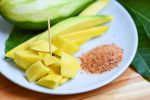 マンゴースライス白いプレートとツリーの熱帯夏のフルーツコンセプト-完熟マンゴーピクルスフルーツとスナックのグリーンマンゴーの葉