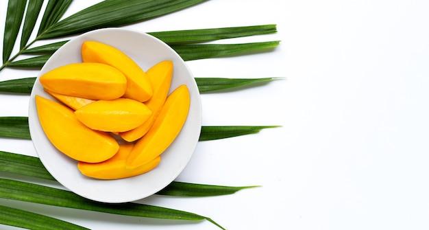 Ломтики манго на белой тарелке на тропических пальмовых листьях. вид сверху