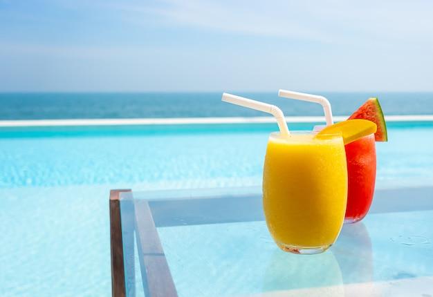 Коктейль из манго и коктейль из арбуза с бассейном и морским пляжем