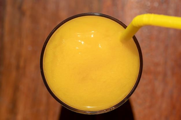 Смузи из манго в стакане на деревянных фоне. коктейль из желтого манго. концепция тропических фруктов. вид сверху, крупным планом