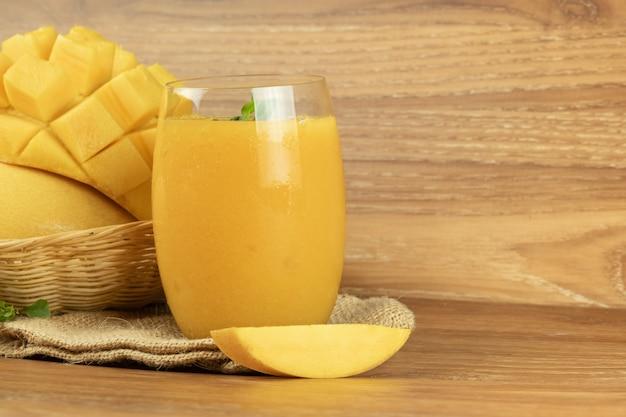 Mango smoothie juice. wooden background.