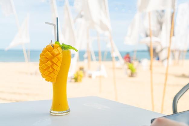Стакан смузи из манго на фоне морского пляжа