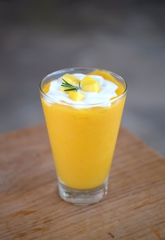 Mango smoothies and yogurt on top in a glass. tropical fruit summer drink.