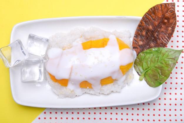 Клейкий рис с манго в тарелке с цветным фоном