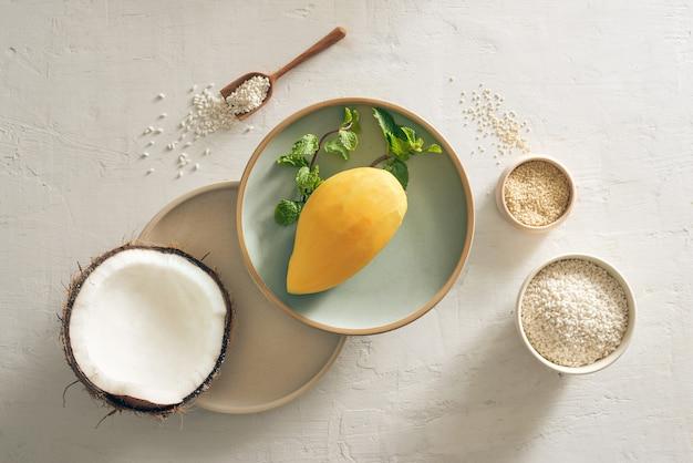 Клейкий рис из манго с рисом, кокосовым молоком и сахаром, кунжутом и фоном манго