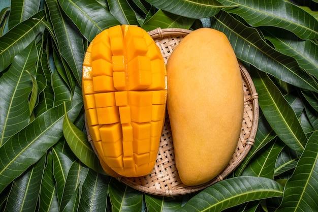 マンゴー、トロピカルフルーツ、緑の葉の背景に竹の木製ふるいバスケット、上面図、フルフレーム、美しく、熟した収穫のデザインコンセプト。