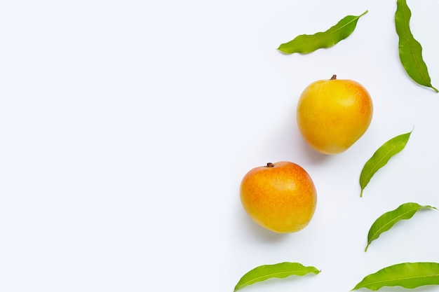 Mango, tropical fruit with leaves on white background. top view