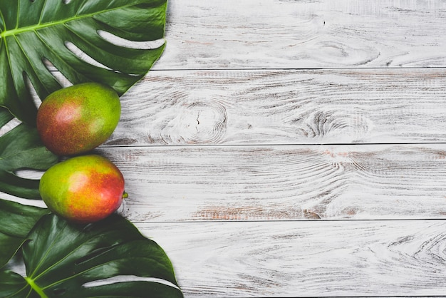 Mango. tropical fruits. on wooden table. top view.