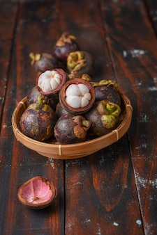 Плоды мангустана в бамбуковой корзине на деревянном столе