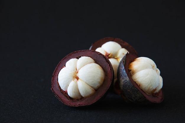 Мангостин из популярных тайских фруктов - тропический фрукт со сладкими сочными белыми кусочками мякоти внутри толстой красновато-коричневой кожуры.