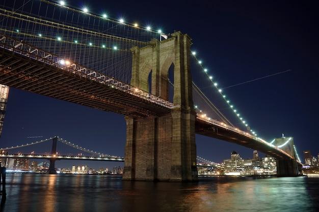 マンハッタン橋とブルックリンのスカイライン、夜の川の反射がぼやけています。