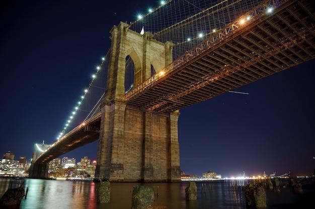 밤에 강에 흐릿한 반사가 멋진 맨해튼 다리와 브루클린 스카이라인