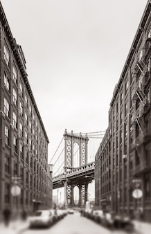 Вид на манхэттенский мост и эмпайр-стейт-билдинг из бруклина, нью-йорк. черно-белое изображение с размытым передним планом. стилизация старых фотографий, добавлена зернистость пленки. тонированная сепия