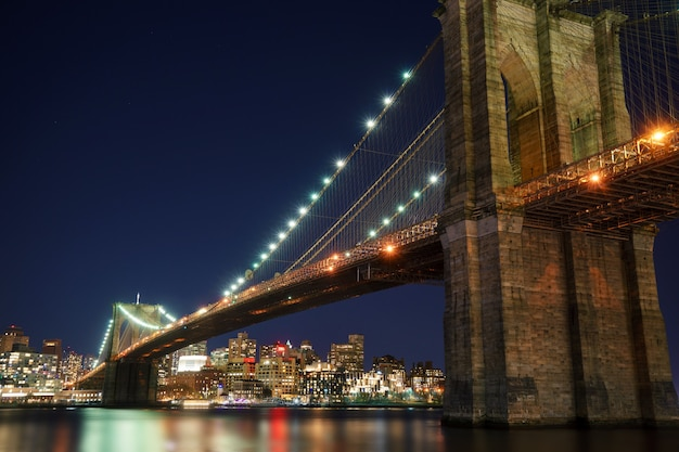 Manhattan bridge and brooklyn skyline with nice blurred reflection in the river at night