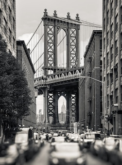 Manhattan bridge and empire state building seen from brooklyn, new york. black and white image with a blurred foreground