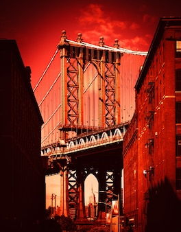 Manhattan bridge with the empire state building and brick wall buildings viewed from dumbo, brooklyn, new york