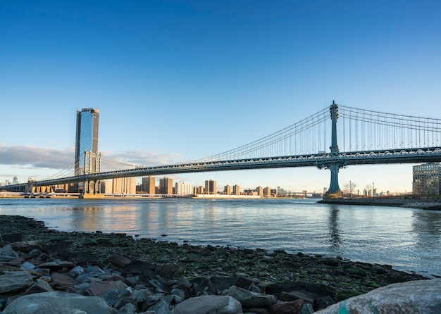 マンハッタン橋とマンハッタンのスカイライン、朝にはニューヨーク市のイーストリバーにカラフルな光。