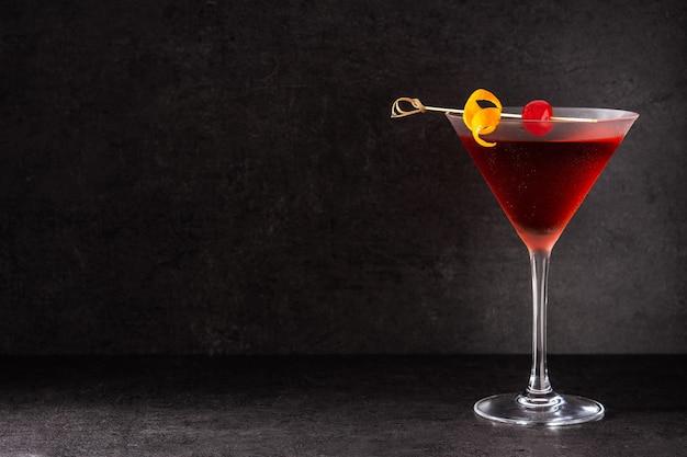 Манхэттенский коктейль с вишней на черном столе Premium Фотографии