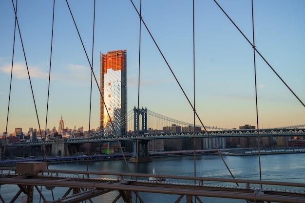 Панорама горизонта города манхэттена с передним планом манхэттенского моста от берега реки бруклинский мост парк, нью-йорк, сша
