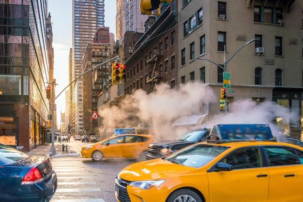 Утренний восход манхэттена с желтыми такси, проезжающими в нью-йорке, сша