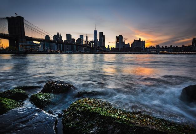 Горизонт манхэттена с бруклинским мостом в вечернее время. скалы и камни на берегу ист-ривер