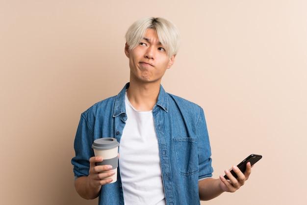 何かを考えながら奪うと携帯電話に若いアジアmanholdingコーヒー