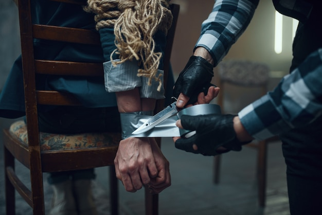 Maniac kidnapper taping his female victim's hands. kidnapping is a serious crime, crazy male psycho, kidnap horror, violence
