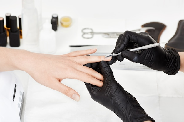 Manicrurist in gloves pushing cuticle on woman's ring finger.