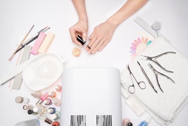 マニキュアとペディキュアのアイテム-マニキュア乾燥ランプ、ネイルファイル、はさみ、明るい表面のブラシ。