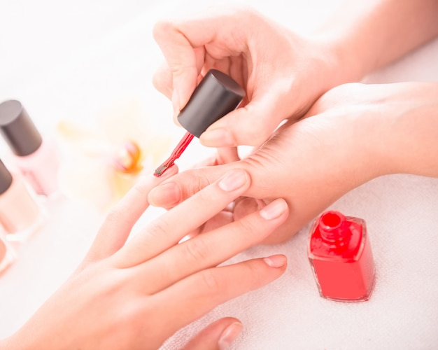 Manicure in the beauty salon woman is drawing of red nail.