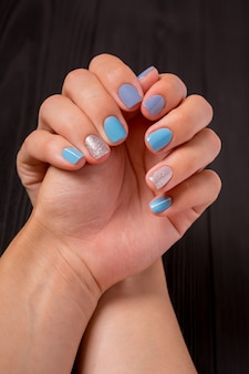 The manicure, blue with silver color, isolated on a black wooden background