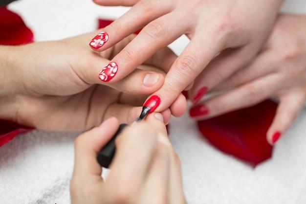 マニキュア。ビューティーサロンで赤いマニキュアで爪を磨く美しい女性の手のクローズアップ。美容師の手の絵画の女性のクライアントの爪のクローズアップ。美容コンセプト。高解像度
