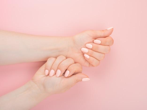マニキュアのコンセプト。ピンクの背景に美容院で完璧なマニキュアと美しい女性の手。マニキュアを受けているネイルサロンの女性。衛生と手のケア。美容業界のコンセプト。