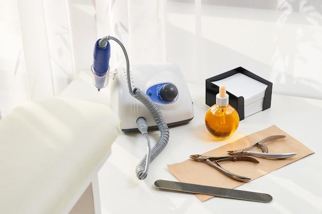 マニキュア機器。ホームマニキュアとネイルケア用に設定します。マニキュアまたはペディキュアセットツールは、美容院の白いタオルでテーブルに置かれます。ビューティーショップやビューティーパーラーの設備